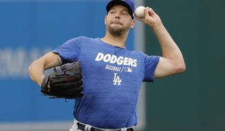 Los Angeles Dodgers starting pitcher Rich Hill warms up before Game3 of a baseball National League Division Series against the Washington Nationals, Sunday, Oct. 6, 2019, in Washington. (AP Photo/Julio Cortez)