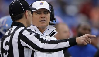 Kansas head coach Les Miles talks to an official during the first half of an NCAA college football game against Oklahoma, Saturday, Oct. 5, 2019, in Lawrence, Kan. (AP Photo/Charlie Riedel)