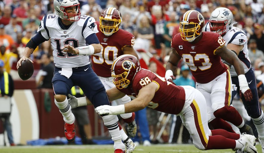 New England Patriots quarterback Tom Brady (12) works under pressure in the pocket against Washington Redskins defensive end Matthew Ioannidis (98) during the first half of an NFL football game, Sunday, Oct. 6, 2019, in Washington. (AP Photo/Patrick Semansky)