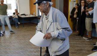 An elderly man walks to a voting booth to fill his ballot paper at a polling station in Lisbon Sunday, Oct. 6, 2019. Portugal is holding a general election Sunday in which voters will choose members of the next Portuguese parliament. (AP Photo/Armando Franca)