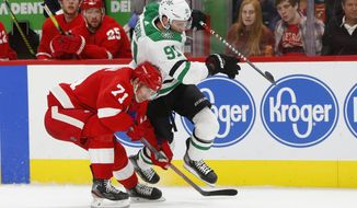 Dallas Stars center Tyler Seguin (91) and Detroit Red Wings center Dylan Larkin (71) chase the puck in the first period of an NHL hockey game Sunday, Oct. 6, 2019, in Detroit. (AP Photo/Paul Sancya)