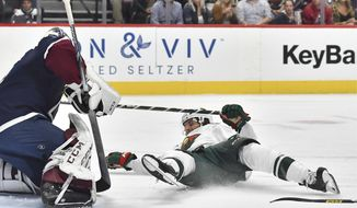Minnesota Wild right wing Ryan Hartman (38) falls to the ice as he was tripped up by Colorado Avalanche defenseman Ryan Graves (27) during the second period in an NHL hockey game Saturday, Oct. 5, 2019 in Denver. Colorado Avalanche defenseman Ryan Graves was penalized on the play. (AP Photo/John Leyba)