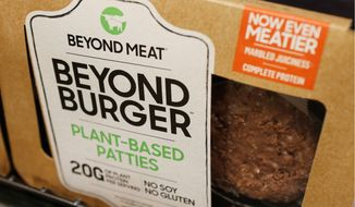 In this June 27, 2019, file photo a meatless burger patty called Beyond Burger made by Beyond Meat is displayed at a grocery store in Richmond, Va. Shares of Beyond Meat are tumbling in Thursday, Aug. 1, premarket trading after the plant-based meat maker priced a secondary stock offering at more than six times its initial public offering opening price. (AP Photo/Steve Helber, File)