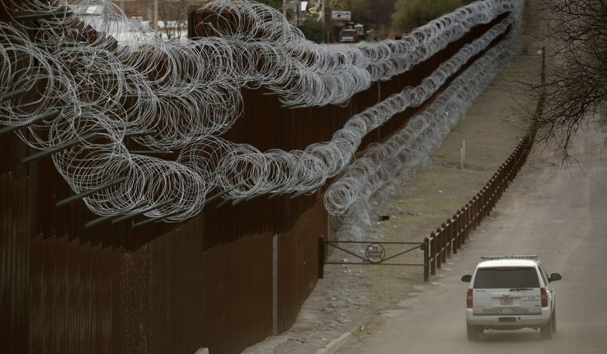 FILE - In this March 2, 2019 file photo a Customs and Border Control agent patrols on the US side of a razor-wire-covered border wall that separates Nogales, Mexico from Nogales, Ariz. A U.S. Border Patrol agent has died after being found unresponsive while on patrol near the Arizona border, but authorities say there's no evidence of foul play. The agency's Tucson sector says in a Monday, Oct. 7, 2019, statement that agents on Sunday found 44-year-old Robert Hotten unresponsive near Mount Washington south of Patagonia in southeastern Arizona. He was patrolling alone, which is customary. (AP Photo/Charlie Riedel,File)