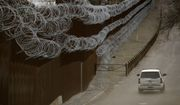 In this March 2, 2019 file photo a Customs and Border Control agent patrols on the US side of a razor-wire-covered border wall that separates Nogales, Mexico from Nogales, Ariz. A U.S. Border Patrol agent has died after being found unresponsive while on patrol near the Arizona border, but authorities say there's no evidence of foul play. The agency's Tucson sector says in a Monday, Oct. 7, 2019, statement that agents on Sunday found 44-year-old Robert Hotten unresponsive near Mount Washington south of Patagonia in southeastern Arizona. He was patrolling alone, which is customary. (AP Photo/Charlie Riedel,File)