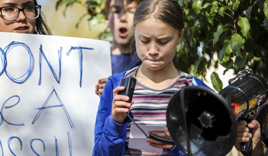 Greta Thunberg pauses and looks at her notes while speaking during the Climate Change Rally and Marchduring the Climate Change Rally and March Monday, Oct. 7, 2019 in Rapid City, S.D. (Adam Fondren/Rapid City Journal via AP)