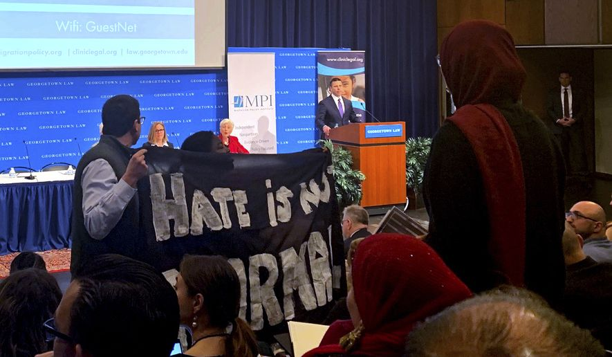 Acting Homeland Security Secretary Kevin McAleenan takes the podium at a immigration law and policy conference, Monday, Oct. 7, 2019 in Washington.  As he took the stage, a handful of protesters stood up and held large black banners, one read Hate is Not Normal, and shouted out that children were under attack. They also began yelling the names of children who had died after they were in immigration custody. McAleenan was scheduled as the keynote speaker at Georgetown University Law Center during an annual immigration law and policy conference held by the nonprofit immigration think tank Migration Policy Institute.  (AP Photo/Colleen Long