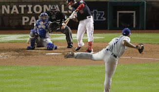 Washington Nationals' Anthony Rendon (6) hits an RBI-single off Los Angeles Dodgers relief pitcher Julio Urias (7) during the fifth inning in Game 4 of a baseball National League Division Series, Monday, Oct. 7, 2019, in Washington. Nationals Trea Turner scored on the hit. (AP Photo/Julio Cortez)