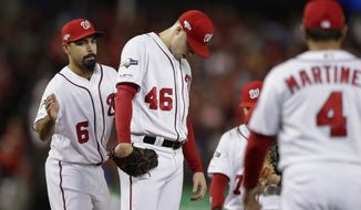 Washington Nationals pitcher Patrick Corbin, lowers his head as manager Dave Martinez, right, walks over during a pitching change in the sixth inning against the Los Angeles Dodgers during Game 3 of a baseball National League Division Series on Sunday, Oct. 6, 2019, in Washington. Patting Corbin on the back Anthony Rendon (6). Corbin was charged with six of the Dodgers' seven runs in the inning. The Dodgers won 10-4. (AP Photo/Julio Cortez)