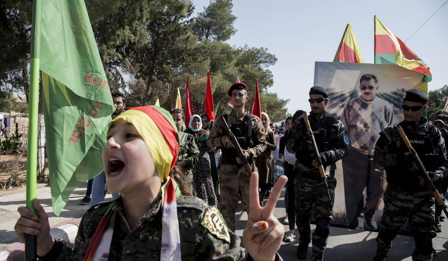 Fighters of the Syrian Democratic Forces, SDF, march during a demonstration against possible Turkish military operation in their areas in Al-Qahtaniya, Syria, Monday, Oct. 7, 2019. Syria's Kurds accused the U.S. of turning its back on its allies and risking gains made in the fight against the Islamic State group as American troops began pulling back on Monday from positions in northeastern Syria ahead of an expected Turkish assault. (AP Photo/Baderkhan Ahmad)