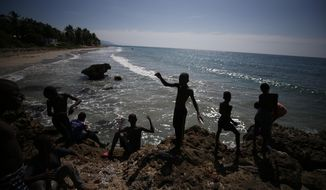Youths fish with bits of line on the coast near Jacmel, Haiti, Sunday, Oct. 6, 2019. Weeks of political turmoil are hitting cities and towns outside the capital of Port-au-Prince especially hard, forcing non-government organizations to suspend aid as barricades cut off the flow of goods between the city and the countryside. (AP Photo/Rebecca Blackwell)