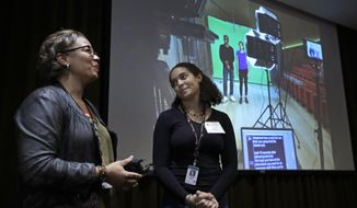 In this Oct. 2, 2019 photo, Museum of Fine Arts' chief of learning and community engagement Makeeba McCreary, left, and student actor Jennifer Rosa, present a video describing a new protocol for student group visits at the museum in Boston. The MFA has made changes in response to accusations of racism after an incident last spring when black middle school students said they were harangued and mistreated on a class trip by white museum patrons and a staff member. (AP Photo/Elise Amendola)