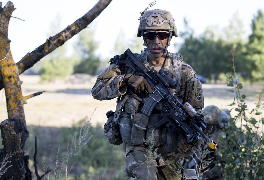 """In this Saturday, June 9, 2018, file photo, a U.S. paratrooper of the 82nd Airborne Division from Fort Bragg in North Carolina takes part in a military exercise """"Saber Strike 2018"""" at the Gaiziunai Training Area some 130 kms (80 miles) west of the capital Vilnius, Lithuania. (AP Photo/Mindaugas Kulbis) ** FILE **"""