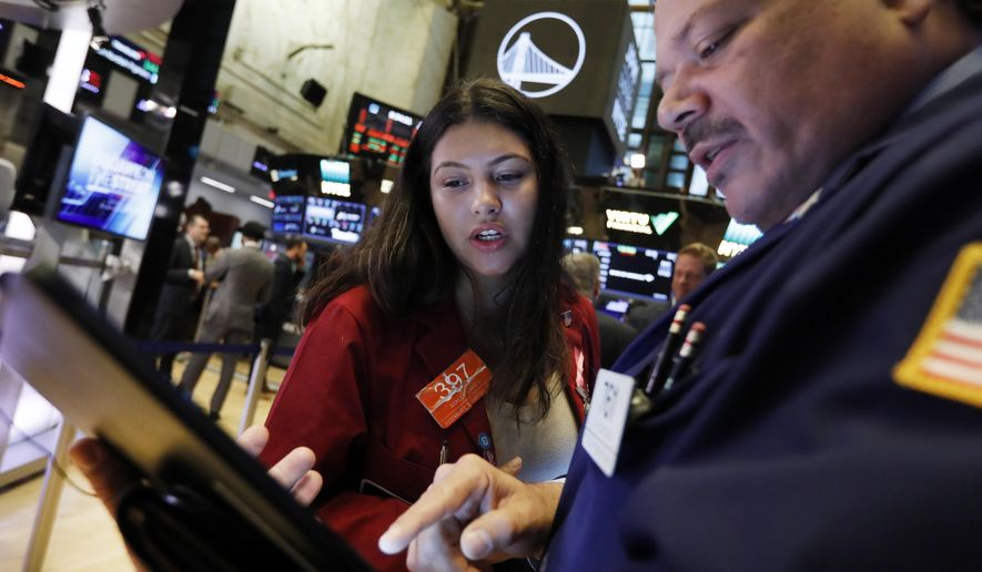 Traders Ashley Lara and John Santiago confer as they work on the floor of the New York Stock Exchange, Monday, Oct. 7, 2019. Stocks are opening broadly lower on Wall Street, extending the market's losing streak into a fourth week. (AP Photo/Richard Drew)