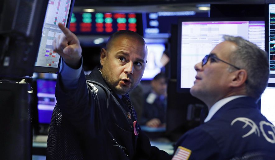 Specialists Mario Picone, left, and Anthony Rinaldi work on the floor of the New York Stock Exchange, Monday, Oct. 7, 2019. Stocks are opening broadly lower on Wall Street, extending the market's losing streak into a fourth week. (AP Photo/Richard Drew)