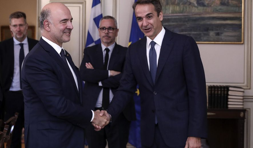 Greece's Prime Minister Kyriakos Mitsotakis, right, shakes hands with the outgoing European Commissioner for Economic and Financial Affairs Pierre Moscovici at Maximos Mansion during their meeting in Athens, Friday, Oct. 4, 2019. The former French finance minister has been credited by Greece with helping keep the country in the euro area during years of financial crisis. He is due to hold talks in Athens on Greece's draft 2020 budget. (AP Photo)
