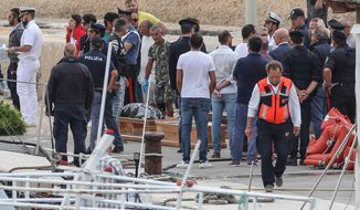 Coffins are prepared on the dock of the tiny island of Lampedusa, Sicily, in southern Italy, Monday, Oct. 7, 2019. At least 13 people died when an overloaded migrant boat capsized near the island of Lampedusa as they were about to be rescued, the Italian Coast Guard said Monday. Twenty-two people were rescued from the sea and taken to land. (Pasquale Claudio Montana Lampo/ANSA via AP)