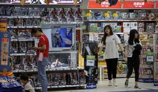 FILE - In this May 23, 2019, file photo, customers shop near a section selling Marvel Avengers toys by American toymaker Hasbro at a toy store in Beijing. The nation's business economists think President Donald Trump's trade war with China will contribute to a sharp slowdown in economic growth this year and next, raising concerns about a possible recession starting late next year. (AP Photo/Andy Wong, File)