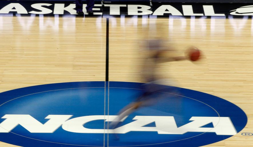 In this March 14, 2012, file photo, a player runs across the NCAA logo during practice at the NCAA tournament college basketball in Pittsburgh. The NCAA is on its heels again, playing defense of its archaic amateurism rules after missing an opportunity to get out in front of an issue.  (AP Photo/Keith Srakocic, File) **FILE**
