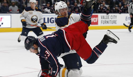 Buffalo Sabres defenseman Jake McCabe, top, upends Columbus Blue Jackets forward Cam Atkinson during the second period of an NHL hockey game in Columbus, Ohio, Monday, Oct. 7, 2019. (AP Photo/Paul Vernon)