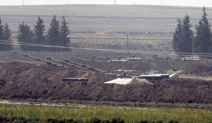 In this Sunday, Oct. 6, 2019, photo, Turkish forces artillery pieces are seen on their new positions near the border with Syria in Sanliurfa province, Turkey. U.S.-backed Kurdish-led forces in Syria said American troops began withdrawing Monday from their positions along Turkey's border in northeastern Syria, ahead of an anticipated Turkish invasion that the Kurds say will overturn five years of achievements in the battle against the Islamic State group. (DHA via AP)