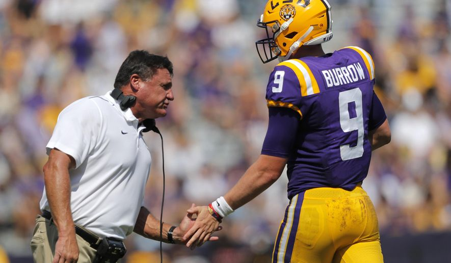 LSU head coach Ed Orgeron congratulates quarterback Joe Burrow (9) after he scored a touchdown in the first half of an NCAA college football game against Utah State in Baton Rouge, La., Saturday, Oct. 5, 2019. (AP Photo/Gerald Herbert)