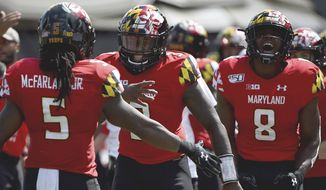 In this Sept. 7, 2019, file photo, Maryland Terrapins running back Anthony McFarland Jr. (5) celebrates with Tyrrell Pigrome (3) and Tayon Fleet-Davis (8) after scoring a touchdown against Syracuse during the first half of an NCAA college football game, in College Park, Md. Maryland's annual quarterback shuffle appears set to continue, as Josh Jackson's ankle injury sets the stage for Tyrrell Pigrome to get his first start of the season Saturday at Purdue. (AP Photo/Will Newton) **FILE**