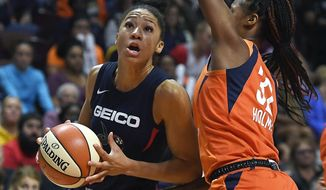 Washington Mystics' Aerial Powers, left, drives to the basket as Connecticut Sun's Bria Holmes defends during the second half in Game 4 of basketball's WNBA Finals, Tuesday, Oct. 8, 2019, in Uncasville, Conn. (AP Photo/Jessica Hill) ** FILE **
