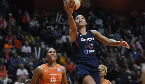 Washington Mystics' Natasha Cloud drives to the basket past Connecticut Sun's Alyssa Thomas, left, and Courtney Williams, right, during the second half in Game 4 of basketball's WNBA Finals, Tuesday, Oct. 8, 2019, in Uncasville, Conn. (AP Photo/Jessica Hill)
