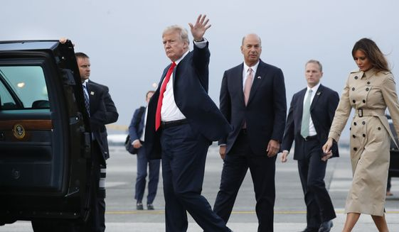 President Donald Trump, center, waves to members of the media as he walks with the U.S. ambassador to the European Union, Gordon Sondland, second from the right, on the tarmac after Trump's arrival, with first lady Melania Trump, far right, on Air Force One at Melsbroek Air Base, Tuesday, July 10, 2018 in Brussels, Belgium. (AP Photo/Pablo Martinez Monsivais) ** FILE **