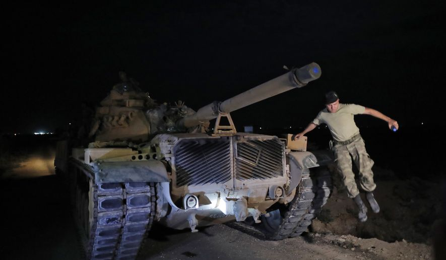 A Turkish army officer jumps from his tank moving to its new position on the Turkish side of the border between Turkey and Syria, in Sanliurfa province, southeastern Turkey, Tuesday, Oct. 8, 2019. Tensions have risen at the border between Turkey and Syria, on expectation of a Turkish military incursion into Syria. (AP Photo/Lefteris Pitarakis)