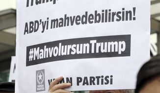 """A Turkish man holds a placard that reads """"Trump, you can only destroy the USA!"""" during a protest near the U.S. embassy in Ankara, Turkey, Tuesday, Oct. 8, 2019. Turkey's vice president Fuat Oktay says his country won't bow to threats in an apparent response to U.S. President Donald Trump's warning to Ankara about the scope of its planned military incursion into Syria. (AP Photo/Burhan Ozbilici)"""