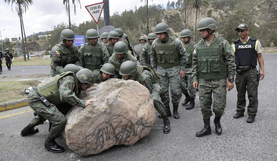 Soldiers work to remove a boulder place there by protesters to block the Simon Bolivar highway in Quito, Ecuador, Monday, Oct. 7, 2019. President Lenin Moreno, who earlier declared a state of emergency over a transportation strike, vowed Friday that he wouldn't back down on the decision to end costly fuel subsidies, which doubled the price of diesel overnight and sharply raised gasoline prices. (AP Photo/Dolores Ochoa)