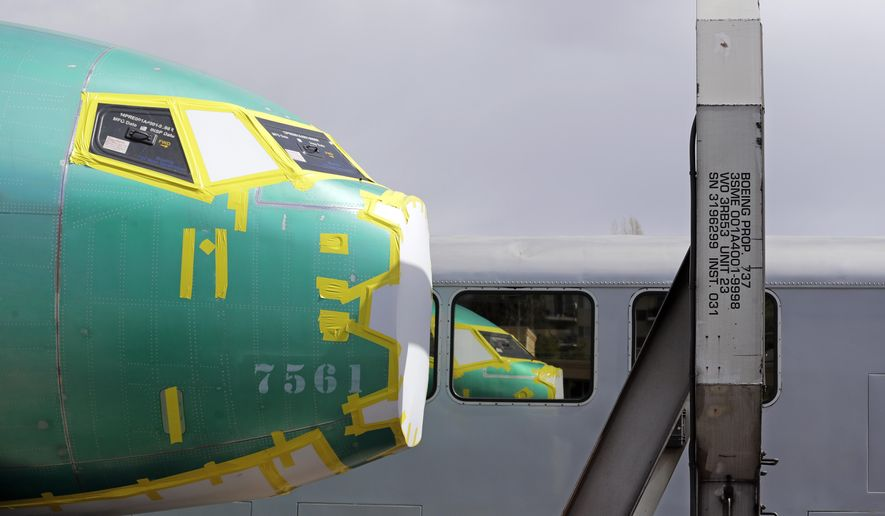 FILE - In this April 9, 2019, file photo the front of a Boeing 737 fuselage, eventually bound for Boeing's production facility in nearby Renton, Wash., sits on a flatcar rail car and is reflected in a nearby passenger train car at a rail yard in Seattle. Boeing said Tuesday, Oct. 8, that it delivered just 26 planes in September, down from 87 a year earlier, when it was ramping up Max production. (AP Photo/Elaine Thompson, File)