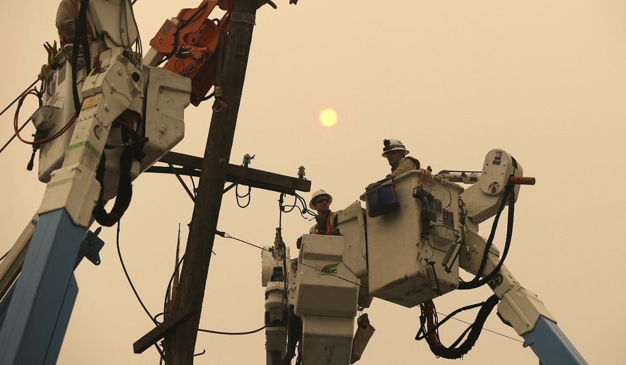 FILE - In this Nov. 9, 2018, file photo, Pacific Gas & Electric crews work to restore power lines in Paradise, Calif. Two years to the day after some of the deadliest wildfires tore through Northern California wine country, two of the state's largest utilities were poised Tuesday, Oct. 8, 2019, to shut off power to more than 700,000 customers in 37 counties, in what would be the largest preventive shut-off to date as utilities try to head off wildfires caused by faulty power lines. (AP Photo/Rich Pedroncelli, File)