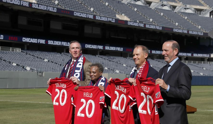 Chicago Fire owner Joe Mansueto, second from right, poses with Chicago Parks Superintendent Michael P. Kelly, left, Mayor Lori Lightfoot, and Major League Soccer Commissioner Don Garber, right, after Mansueto announced that the MLS soccer team will play their 2020 season in Soldier Field Tuesday, Oct. 8, 2019, in Chicago. (AP Photo/Charles Rex Arbogast)