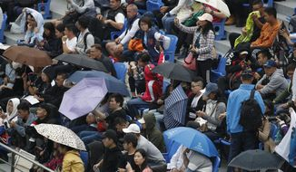 Spectators use umbrellas while watching the men's doubles match between Novak Djokovic and Filip Krajinovic of Serbia and Kevin Krawietz and Andreas Mies of Germany during the men's doubles match at the Shanghai Masters tennis tournament at Qizhong Forest Sports City Tennis Center in Shanghai, China, Tuesday, Oct. 8, 2019. (AP Photo/Andy Wong)