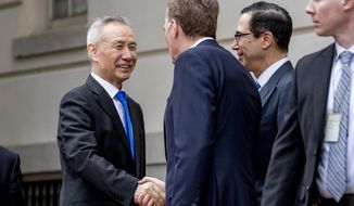 FILE - In this May 10, 2019, file photo, China's Vice Premier Liu He, left is greeted by U.S. Treasury Secretary Steve Mnuchin, second from right, and U.S. Trade Representative Robert Lighthizer, third right, as he arrives at the Office of the United States Trade Representative in Washington. China's Ministry of Commerce said Tuesday that Liu is going to Washington on Thursday for talks aimed at ending the tariff war. (AP Photo/Andrew Harnik, File)