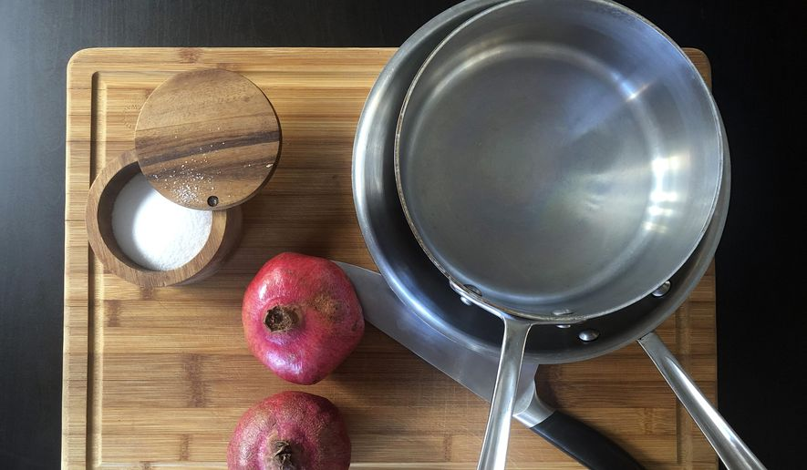 This Oct. 2, 2019 photo shows kosher salt, a couple of pans, a chefs knife and two pomegranates on a cutting board displayed in New York. From avoiding unsalting to making sure you're not working with a dull knife, there are certain mistakes that are pretty easy to avoid in the kitchen, once you know what to look out for. Others include not fiddling with the food while it cooks and not forgetting about carryover cooking. (Katie Workman via AP)