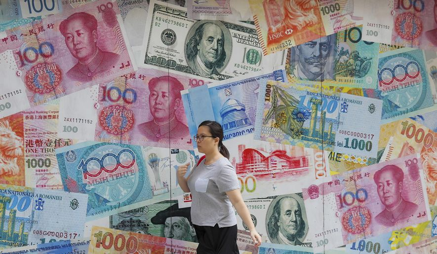 """FILE - In this Aug. 6, 2019, file photo, a woman walks by a money exchange shop decorated with different countries currency banknotes at Central, a business district in Hong Kong. The Hong Kong stock exchange is dropping a bid to buy its London counterpart following opposition from the European exchange's management. Hong Kong Exchanges and Clearing Ltd. said it was """"unable to engage"""" with the London exchange's management on the deal. (AP Photo/Kin Cheung, File)"""