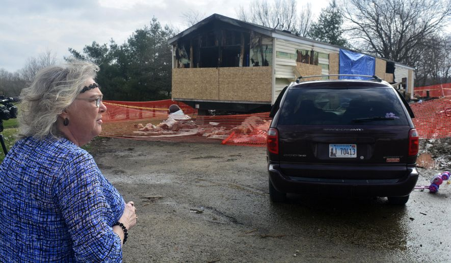 In this Sunday, April 7, 2019, file photo, Marie Chockley, a resident of the Timberline Trailer Court, north of Goodfield, Ill., surveys the damage that was caused by a Saturday night fire that killed five residents in a mobile home. A prosecutor says a central Illinois 9-year-old is expected to be charged Tuesday with five counts of first-degree murder in connection with the deadly mobile home fire. (Kevin Barlow/The Pantagraph via AP, File)