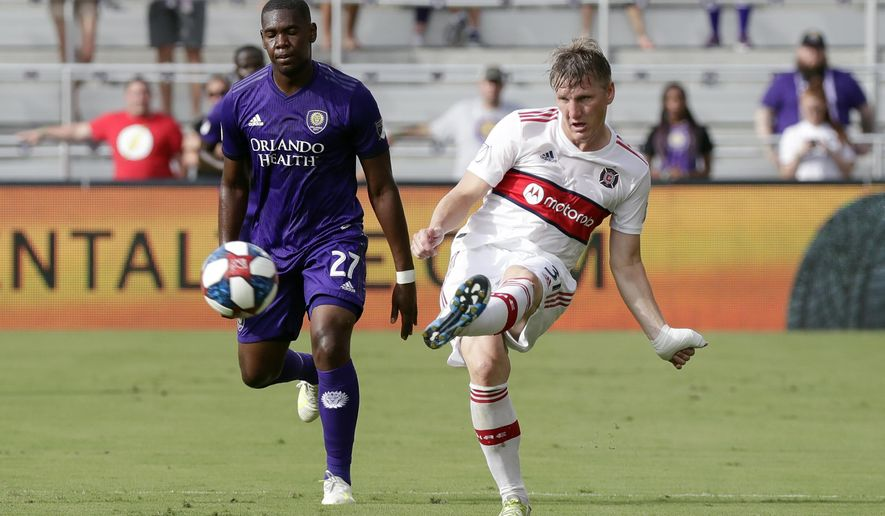 Chicago Fire's Bastian Schweinsteiger, right, passes the ball in front of Orlando City's Kamal Miller (27) during the first half of an MLS soccer match, Sunday, Oct. 6, 2019, in Orlando, Fla. (AP Photo/John Raoux)