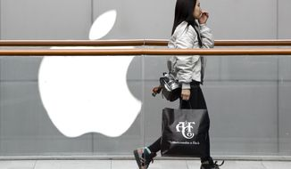 In this Feb. 26, 2019, file photo, a woman carries a paper bag containing goods purchased from American brand Abercrombie & Fitch walks past an Apple store at the capital city's popular shopping mall in Beijing. Companies who do business with China walk a fine line to stay aligned with U.S. values such as freedom of speech and democracy while avoiding offending China, where they stand to make billions of dollars. (AP Photo/Andy Wong, File) **FILE**