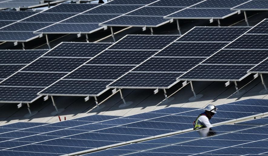 In this Aug. 8, 2019, photo a worker helps to install solar panels onto a roof at the Van Nuys Airport in the Van Nuys section of Los Angeles.  (AP Photo/Richard Vogel)  **FILE**