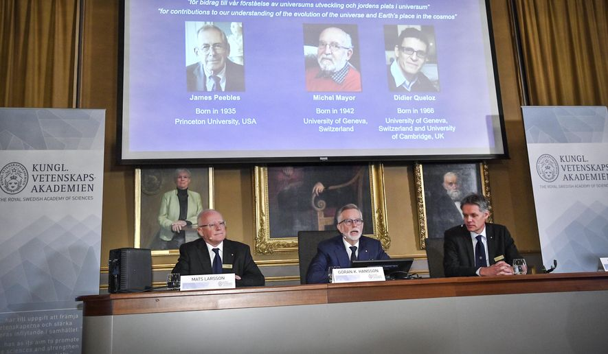 Goran K Hansson, centre, Secretary General of the Royal Swedish Academy of Sciences, and academy members Mats Larsson, left, and Ulf Danielsson, announce the winners of the 2019 Nobel Prize in Physics, during news conference at the Royal Swedish Academy of Sciences in Stockholm, Sweden, on Tuesday Oct. 8, 2019.  The 2019 Nobel Prize in Physics is awarded to, seen from left on the screen, James Peebles, Michel Mayor and Didier Queloz. (Claudio Bresciani / TT via AP)
