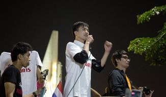 """FILE- in this Feb. 10, 2018, file photo, activist Karn Pongpraphapan addresses the audience during a protest near the democracy monument n Bangkok, Thailand. Police have arrested Karn for his content posted on the internet about how other countries' royal families lost their power and charged him with """"posting content that is a threat to national security."""" (AP Photo, file)"""