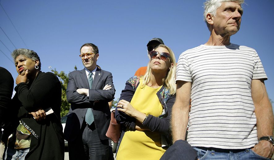 In this Monday, Oct. 7, 2019 photo, Rep. Regina Goodwin, left, Mayor G.T. Bynum, second from left, and others listen to researchers talk about their search for possible mass burial graves from Tulsa's 1921 Race Massacre at Oaklawn Cemetery in Tulsa, Okla. (Mike Simons/Tulsa World/Tulsa World via AP)