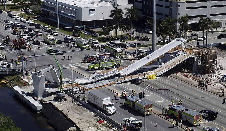 FILE - In this March 15, 2018, file photo, emergency personnel respond after a new pedestrian bridge collapsed onto a highway at Florida International University in Miami. Federal transportation officials say that Louis Berger Group, Inc., the firm charged with reviewing the design of the FIU bridge that collapsed and killed six people, was not properly qualified by the state. (Pedro Portal/Miami Herald via AP, File)