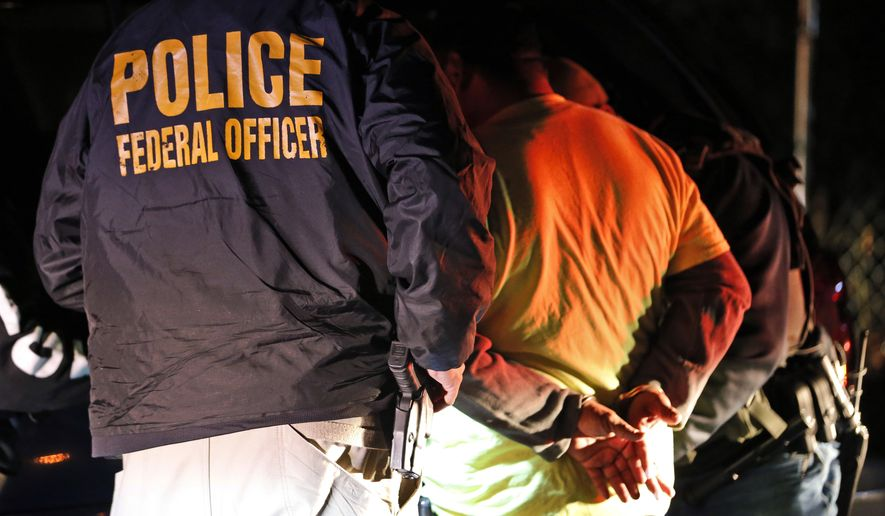 In this Oct. 22, 2018, photo U.S. Immigration and Customs Enforcement agents surround and detain a person during a raid in Richmond, Va. ICE's enforcement and removal operations, like the five-person field office team outside Richmond, hunt people in the U.S. illegally, some of whom have been here for decades, working and raising families. Carrying out President Donald Trump's hard-line immigration policies has exposed ICE to unprecedented public scrutiny and criticism, even though officers say they're doing largely the same job they did before the election, prioritizing criminals. (AP Photo/Steve Helber)