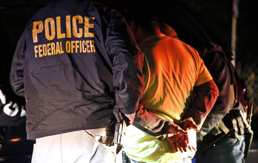In this Oct. 22, 2018, photo U.S. Immigration and Customs Enforcement agents surround and detain a person during a raid in Richmond, Va. (AP Photo/Steve Helber) **FILE**